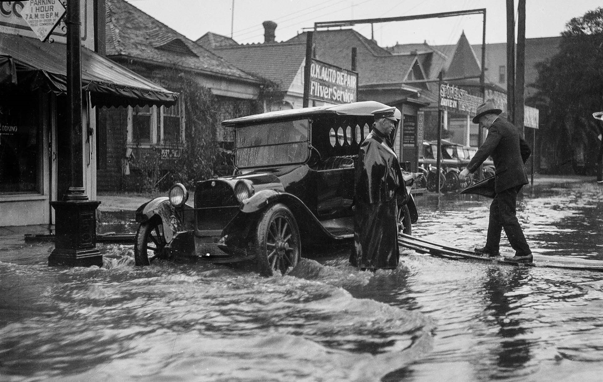 1926 a man is helped to his vehicle on pico boulevard in los angeles during flooding in 1926