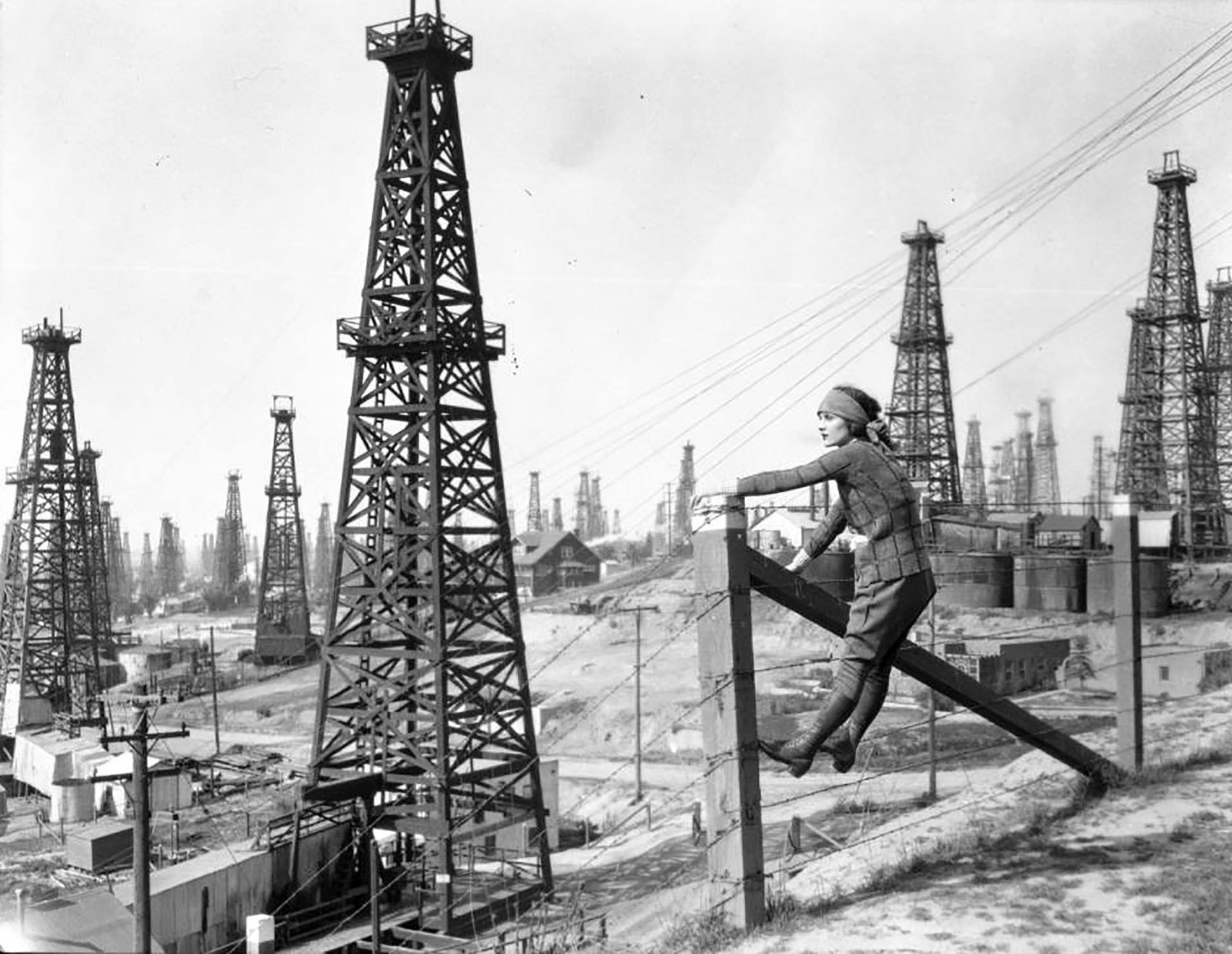 ca 1930s view showing a woman posing on a fence at the signal hill oil field