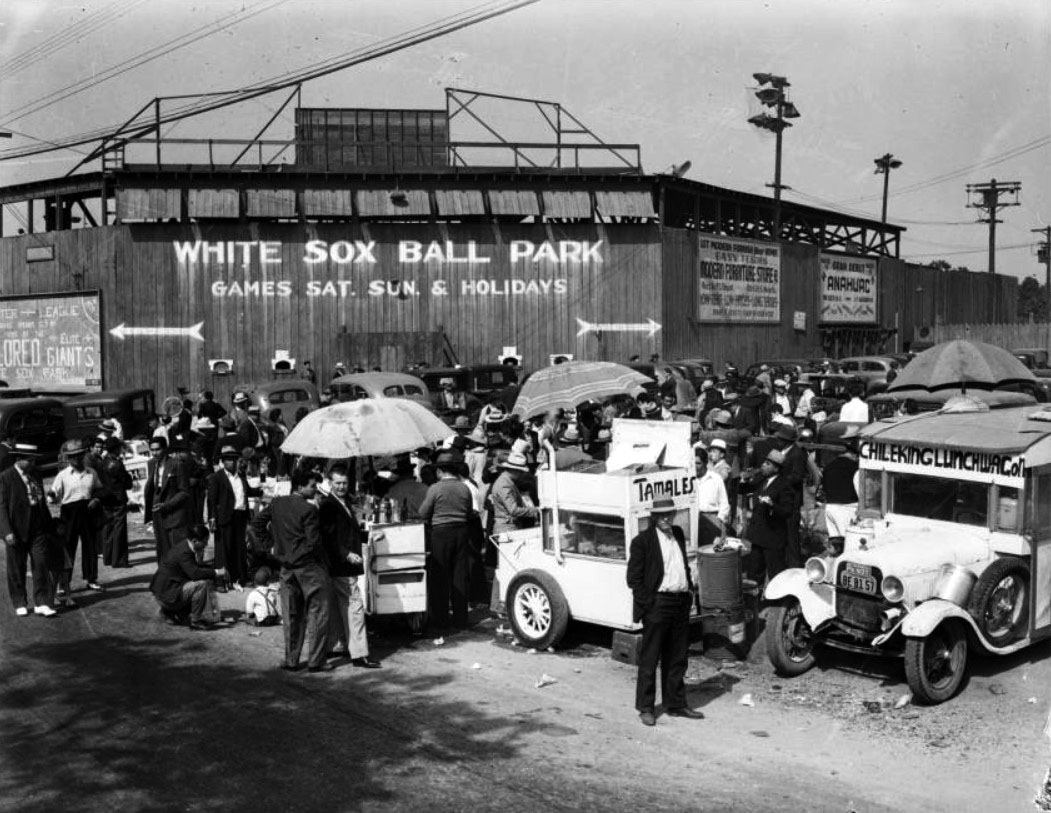 Black and White photo of wooden facade of old baseball field, circa1939. Foreground is cluttred with people, cars and vendor carts. The wall behind them reads