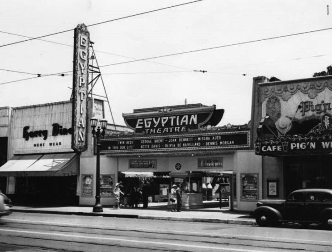 8582bb53a49 (1942)  - View showing the entrance to the Egyptian Theatre with the Pig  N  Whistle Café seen on the right. The marquee reads  Twin Beds with George  Brent
