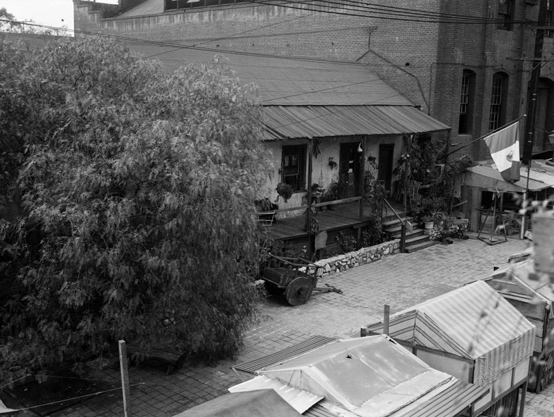 ca 1935 avila adobe as seen from a building across olvera street in front of the house is a wooden cart and a mexican flag is by the entrance adobe tank san francisco ca